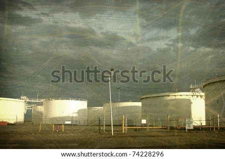 aged vintage photo of oil container tanks with storm clouds in sky