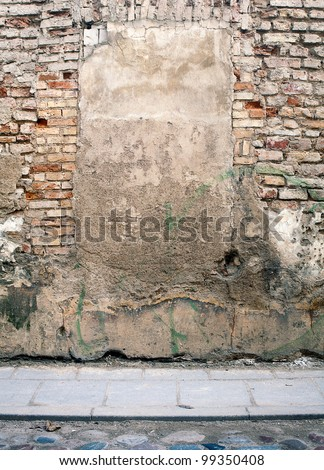 Aged weathered street wall with immured window