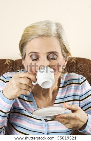 Aged woman drinking a cup of coffee alone and sitting in  a couch