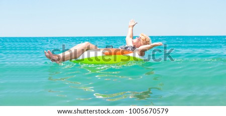 Aged woman floating in a rubber ring in the sea.