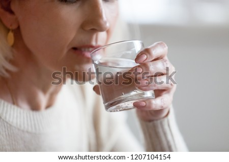 Aged woman holding glass feeling thirsty or dehydrated, senior female drinking fresh pure aqua following healthy lifestyle, elderly lady having still mineral water. Refreshment, dehydration concept