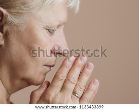 Aged woman prays. Selective focus.