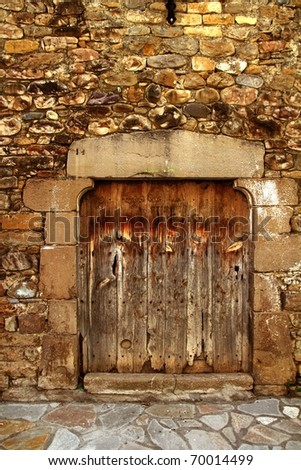 Aged wood door in medieval masonry Pyrenees house facade