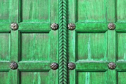 Aged wooden bright green door  with metal bronze rivets on the  wooden textured surface - architectural textured background