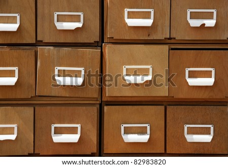 Aged wooden cabinet with square drawers and white handles.