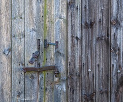 Aged wooden door with old rustic ironmongery, shackle, hasp & staple.