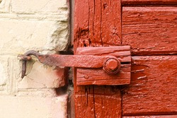 Aged wooden door with old rustic ironmongery, shackle, hasp & staple.  Red door.
