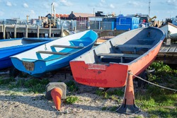 Aged wooden paddle boats are stored beside a wooden jetty near Whitstable beachfront in Kent, England.