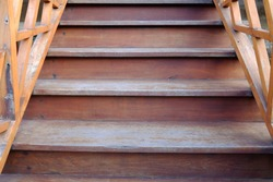 Aged wooden stairways with handrails and day light for background texture