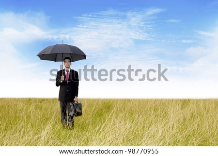 Agent holding umbrella and laptop bag shot outdoor