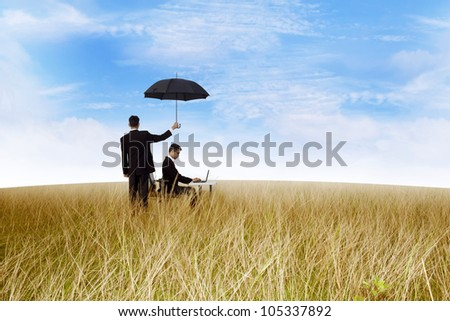 agent in the field with umbrella covering a businessman working outdoor