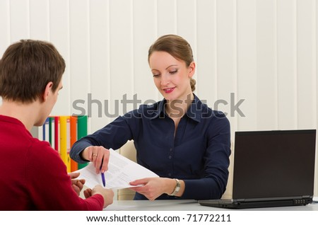 Agent (or notary public) holding pen pointing at signature place on a contract document to man