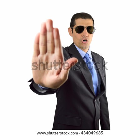 Agent standing on black background and giving the halt with his hand gesturing to stop on white background