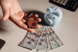 Agent with keys house and blue piggy bank with dollar banknotes. Savings or mortgage concept. Top view
