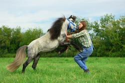 Aggressive animal is attacking and biting young woman in her neck in outdoors, side view. Caucasian female trainer is protecting myself from her angry horse.