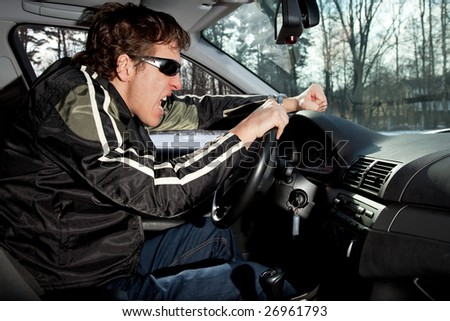 Aggressive driver concept, young man driving aggressively