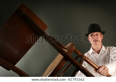 aggressive guy with chair on dark background