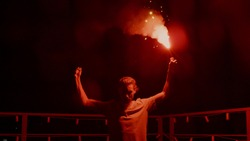 Aggressive man burning signal flare on night roof. Serious football fan standing with red fire outdoors. Man protest concept. Male protester with light at urban background.