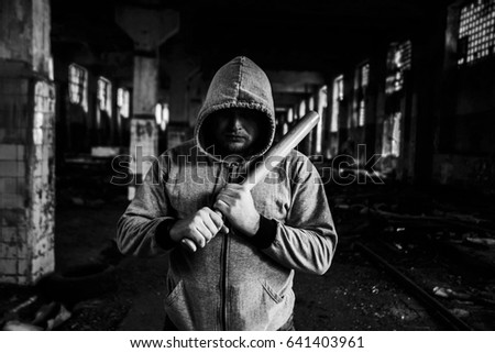 Aggressive man with a baseball bat wear hoody with hood stand inside industrial space room against window frame and beam in perspective