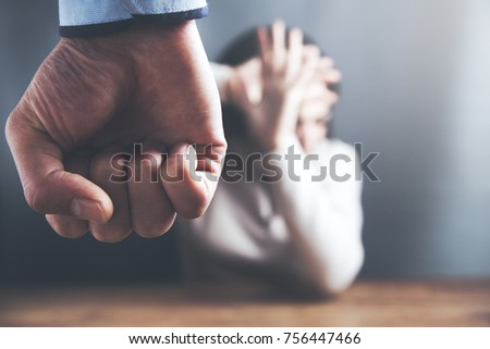 Aggressive man with a clenched fist threatens to hit a scared woman