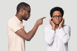 Aggressive millennial african american man shouting, blaming black stressed upset woman, isolated on grey studio background. Unhappy scared irritated girl covering ears with hands, family problems.