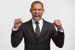 Aggressive mixed race young businessman has clenched fists, shouts loudly at coworkers, being dissatisfied with something, expresses irritation and negative emotions, very angry with someone