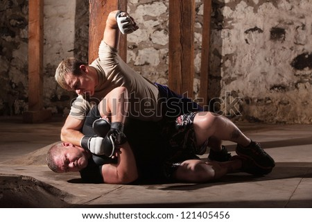 Aggressive MMA fighter punching opponent on the ground