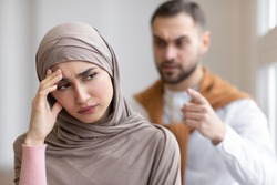 Aggressive Muslim Husband Shouting At Depressed Wife Tired Of Domestic Violence And Victimization Standing At Home. Selective Focus. Relationship With Abuser And Family Conflicts