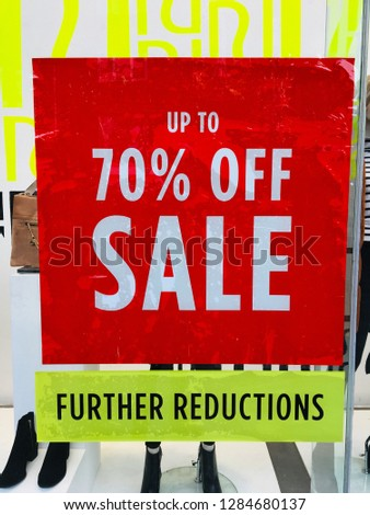 Aggressive retailing with 70 percent off and further reductions in a store window on the high street as retailers compete for holiday sales