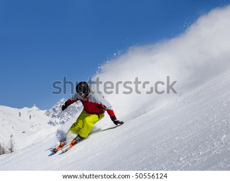 Aggressive skier in the snow  powder skiing fast