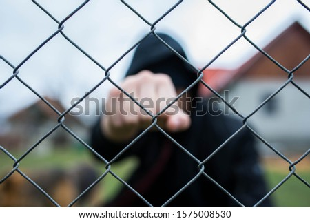 Aggressive  teenage boy showing hes fist behind wired fence at the correctional institute,  focus on the wired fence, conceptual image of juvenile delinquency . #1575008530