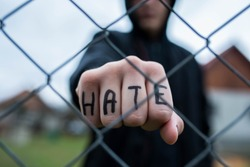 Aggressive teenage boy showing hes fist behind wired fence at the correctional institute, the word hate is written on hes hand, focus on the boys hand , conceptual image of juvenile delinquency .