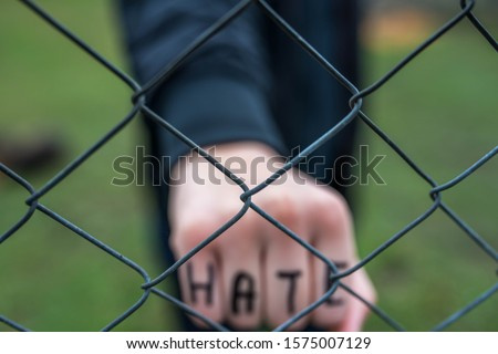 Aggressive  teenage boy showing hes fist behind wired fence at the correctional institute, the word hate is written on hes hand, focus on the wired fence, conceptual image of juvenile delinquency . #1575007129