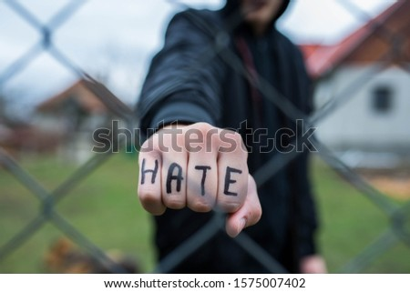 Aggressive teenage boy showing hes fist behind wired fence at the correctional institute, the word hate is written on hes hand, focus on the boys hand , conceptual image of juvenile delinquency . #1575007402