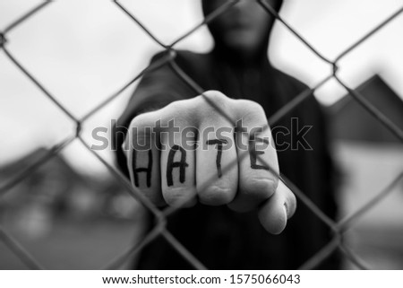 Aggressive teenage boy showing hes fist behind wired fence at the correctional institute, the word hate is written on hes hand, focus on the boys hand , conceptual image of juvenile delinquency . #1575066043
