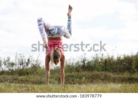 Agile young woman doing a handstand outdoors in the countryside balancing on her hands with her legs bent in opposite directions