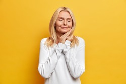 Aging and beauty concept. Charming senior wrinkled Caucasian woman touches face gently stands with closed eyes smiles tenderly enjoys pleasant moment in life isolated on yellow studio background.