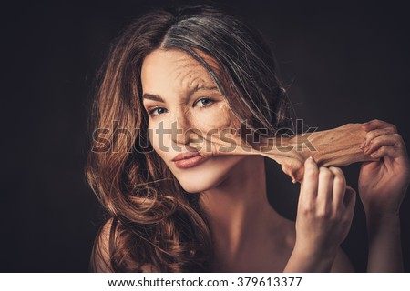 Aging and skin care concept. Half old half young woman, takes off the old skin from the face.