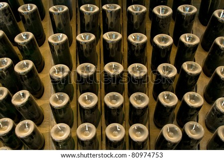 aging champagne bottles in the cellars of the winery #80974753