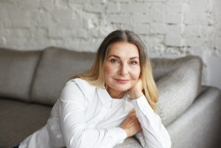 Aging gracefully. Indoor portrait of attractive mature 60 year old female with beautiful blue eyes and healthy wrinkled skin smiling happily at camera while relaxing on grey comfortable sofa at home