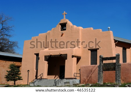 Aging Saint Anthony Church in Dexon, New Mexico has bell tower and crumbling cross steeple.  Stucco building with wooden sign.