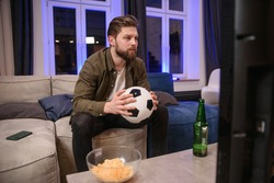 Agitated likable 30-aged bearded guy holding football ball in his hand dissatisfied from the bad game of his favourite team and falling on the couch