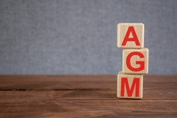 AGM (Annual general meeting) acronym on wooden cubes on dark wooden backround. Business concept.
