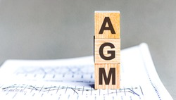 AGM Annual general meeting acronym on wooden cubes on grey backround. Business concept.