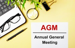 AGM Annual General Meeting is written in red on a white piece of paper on a light yellow background next to a laptop, pen, magnifying glass, glasses and a green plant.