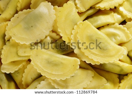agnolotti pasta stuffed with spinach and ricotta cheese on white background
