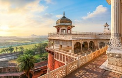 Agra Fort - Medieval Indian fort made of red sandstone and marble with view of dome at sunrise. View of Taj Mahal at a distance as seen from Agra Fort.