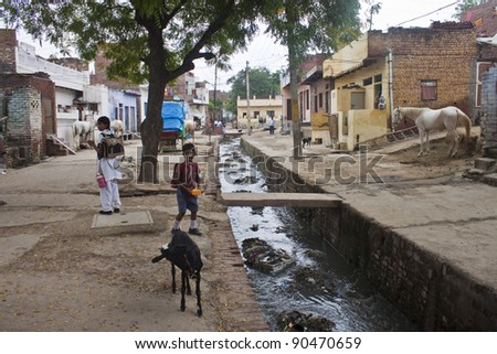 AGRA, INDIA - AUGUST 5: Unidentified children play in a  poor neighborhood on August 5, 2011 in Agra, India. Agra is prominent tourist destination. But still more than half of its population (800,000 people) live in bad conditions. - stock photo