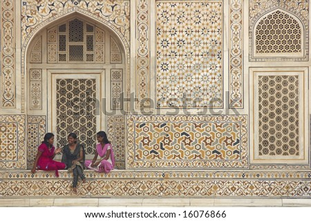 AGRA, INDIA - JULY 26: Unidentified Indian teens in colorful sari's sitting in the alcove of a beautiful Mughal Tomb, I'timad-ud-Daulah. July 26, 2008 in Agra, Uttar Pradesh, India