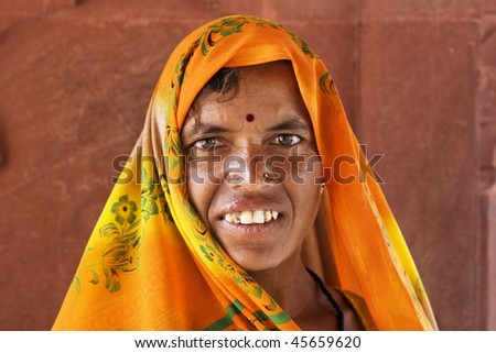 AGRA, INDIA - JUNE 18: An old Indian woman stands in front of the wall of temple on June 18, 2008 in Agra, India. Local women wear colorful saree (sari) as traditional clothing.